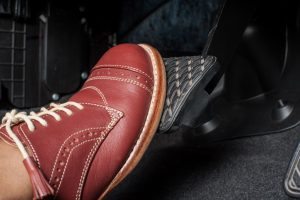 a foot pressing the brake pedal of a car
