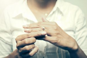 a woman taking off her wedding ring