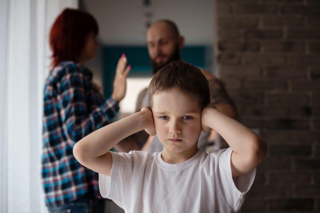 Sad, desperate little boy during parents quarre