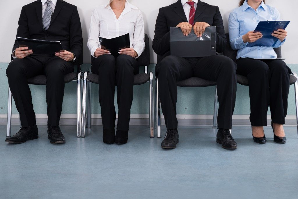 Close-up Of Businesspeople With Files Sitting On Chair waiting for their turn for the interview