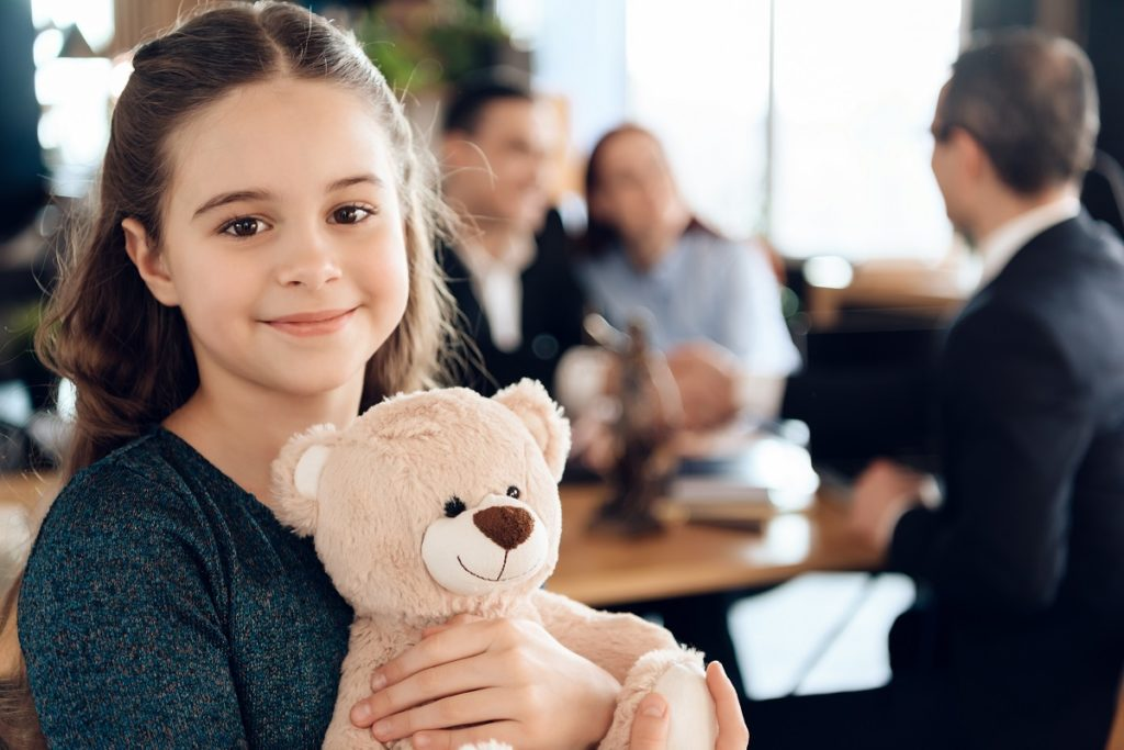 child smiling with her teddy bear